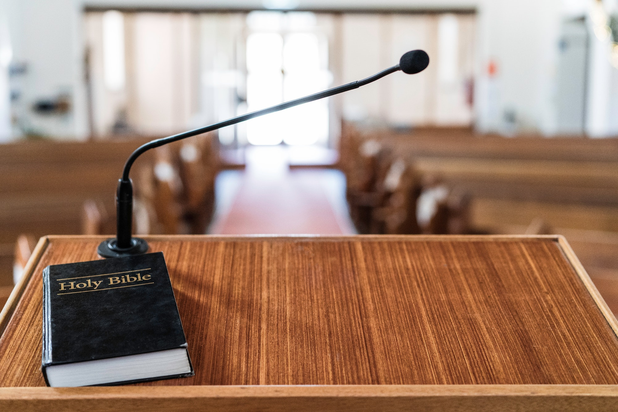 Bible on church pulpit, with light coming through the front doors